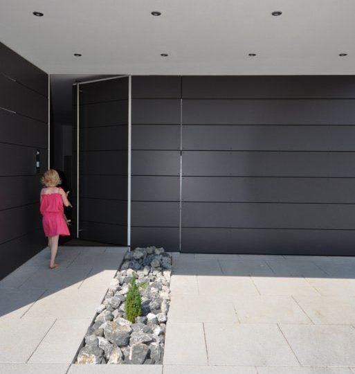 Der Kontrast zwischen dem weißen Putz und der dunklen Verschalung betont die plastische Ausformung des Eingansbereichs.